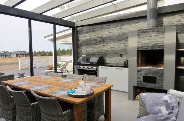 Loma-asunnon kesäkeittiöön on rakennettu moderni harmaa kiviseinä.