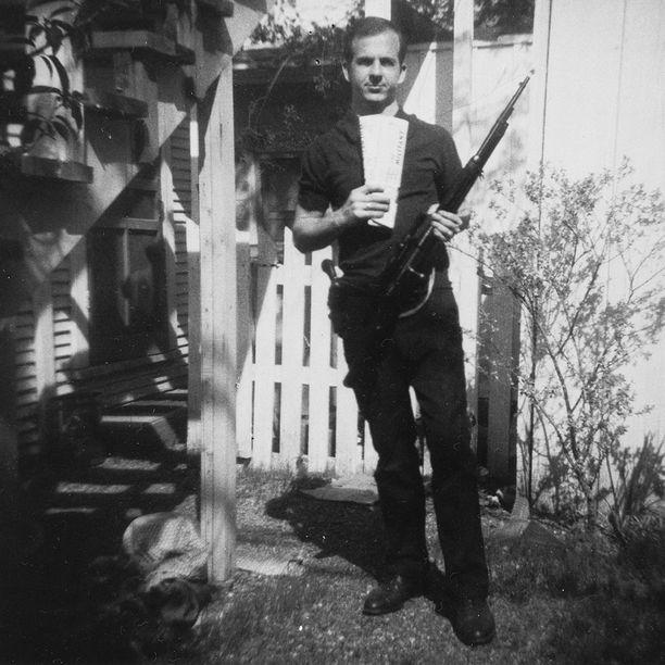 Lee Harvey Oswald poseeraa takapihallaan kiväärinsä kanssa.
