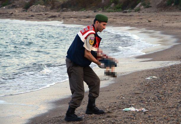 Poliisi kantoi pojan pois rannalta.