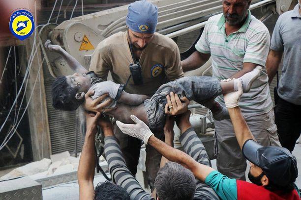 Siviilipuolustustyöntekijät kantoivat Aleppon itäosan pommituksissa kuollutta poikaa.