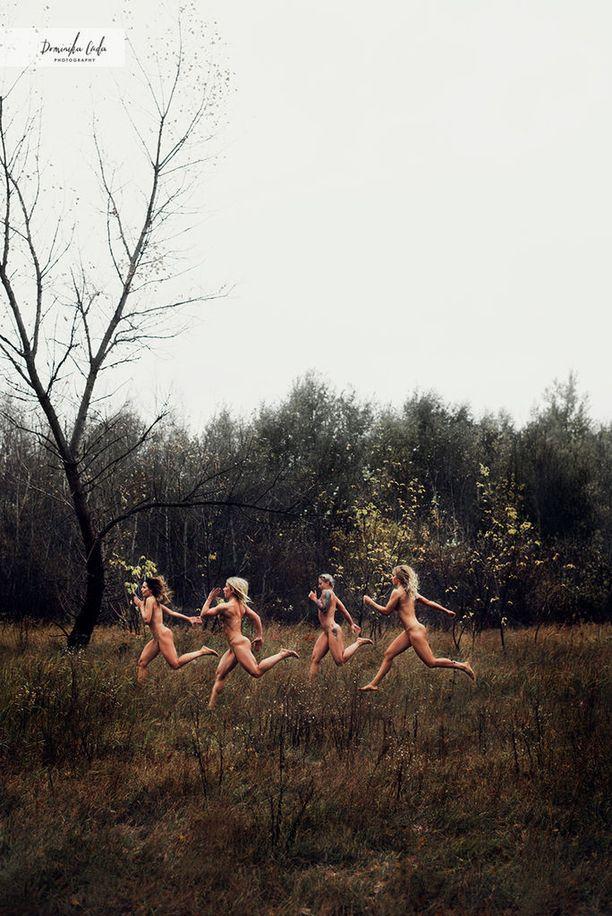 Neljä puolalaisurheilijaa juoksee metsäaukion poikki syyssäässä.