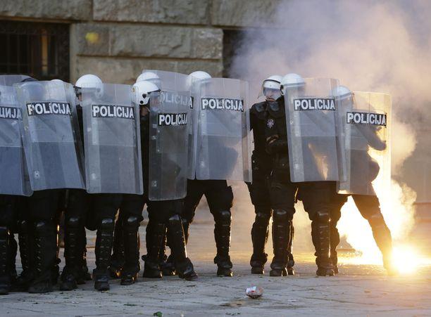 Poliisi vastasi mielenosoittajien soihtuihin kyynelkaasulla ja savulla.