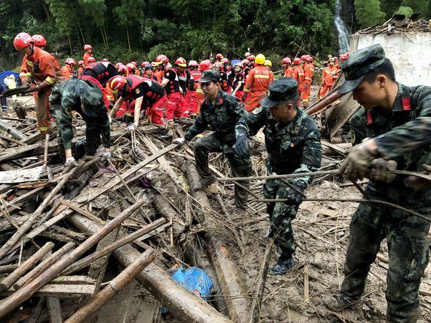 Kiina, Zhejiangin maakunta 11.8.2019. Pelastustyöntekijät raivaavat aluetta maanvyöryn jälkeen.