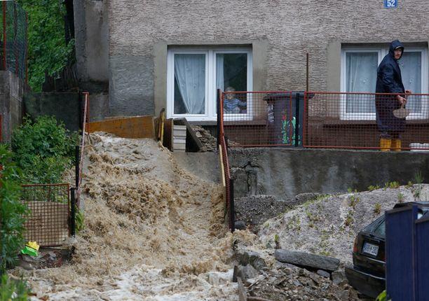 Asukkaat yrittävät suunnata veden virtaamaan pois kodeistaan. Kuvaa Bosniasta torstailta.