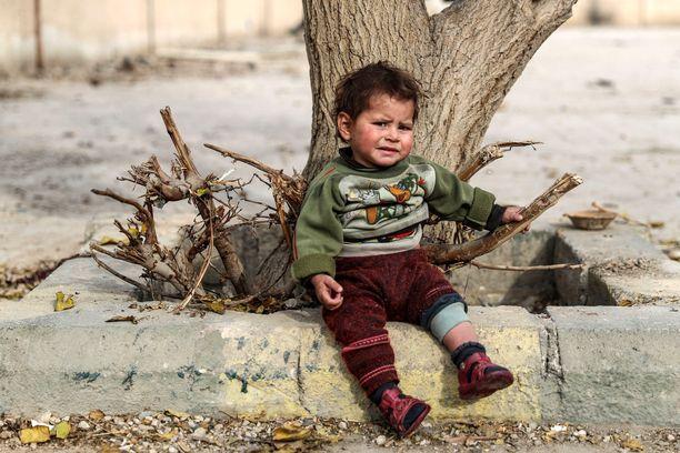 Jouluna 2017 lapsi istui Itä-Ghoutassa pommituksissa tuhoutuneen koulun pihalla.