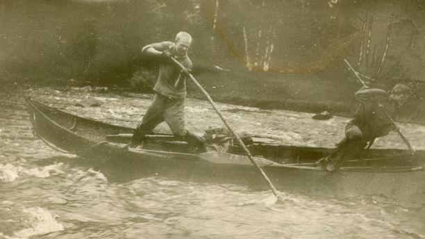 – Mutta koulutien loppusuoralta selviydyttyä oli sentään päällimmäisenä mielessä pääsy elävämmille poluille, metsiin, maille ja vesille. Ja niin lähdinkin kesäkuun alkupuolella, tarkkaan ottaen 4.6., parin toverini kanssa retkeilemään Kongasjoelle, koskiselle joelle, joka laskee Puolangan Osmankajärvestä Paltamon Kivesjärveen, kirjoitti Urho Kekkonen kesäisestä retkestään.Kuvassa miesten vene on karahtanut kiville. Kekkonen ja toinen mies yrittävät irrottaa venettä.