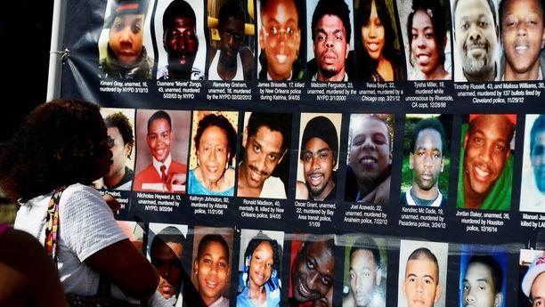 Nainen katseli New Yorkissa kuvia ihmisistä, jotka poliisi on tappanut viime vuosina.