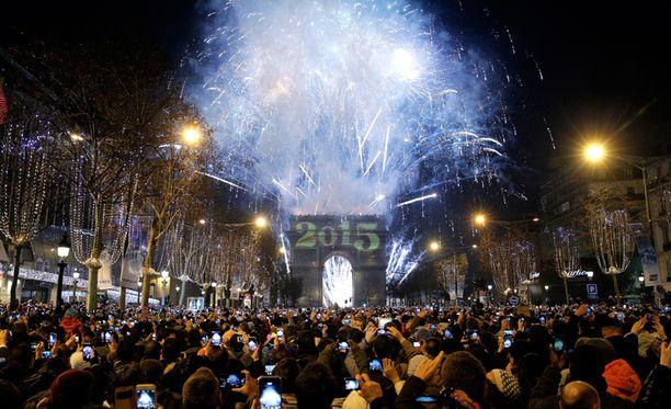 Tuhannet ihmiset olivat juhlimassa uuttavuotta ja katsomassa ilotulituksia Pariisissa Champs-Élysées-kadulla.