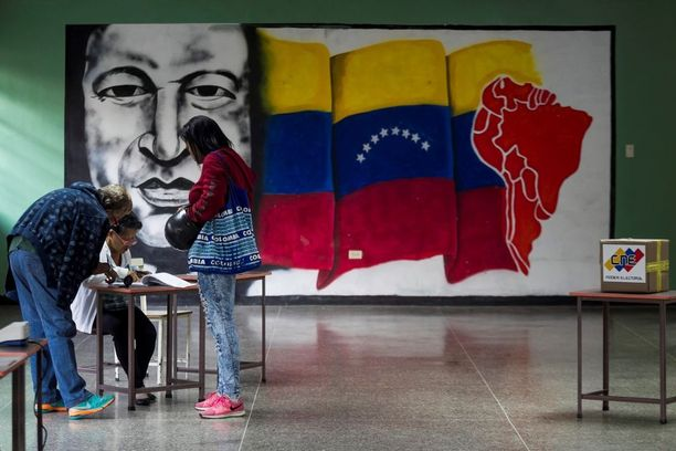 Edesmennyttä presidenttiä Hugo Chavezia esittävä maalaus koristi äänestyspaikan seinää Caracasissa.