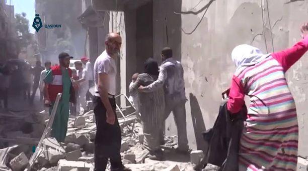 Aleppon asukkaat kävelivät ilmaiskujen jälkeen kivimurskan seassa perjantaina.