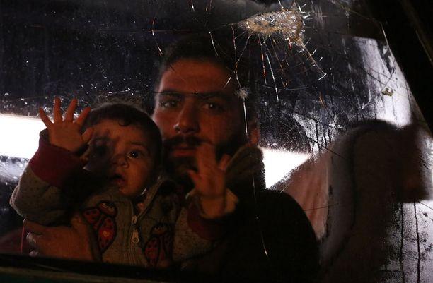 Doumasta Aleppoon paennut syyrialaismies lapsensa kanssa.