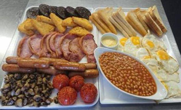 Tällä aamiaisella pärjää pitkälle iltapäivään. Kahdeksan makkaraa, munaa, pekonisiivua, paahtoleipää, perunaröstiä ja veripalttua. Lisäksi papuja ja muita kasviksia.