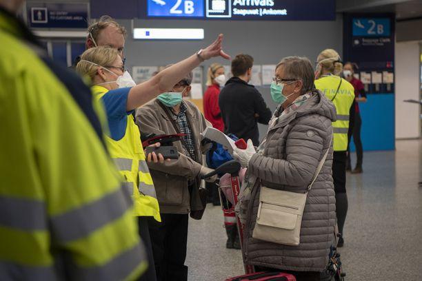 Lentokentällä ohjataan edelleen saapuvia matkustajia.