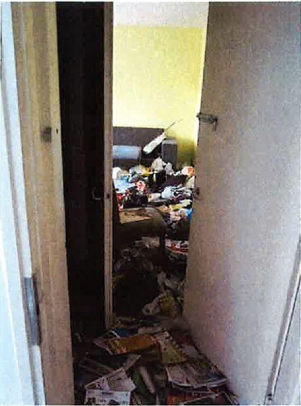 Ulko-oven edessä oli lehtiä ja sisemmällä näkyi jätekasoja.