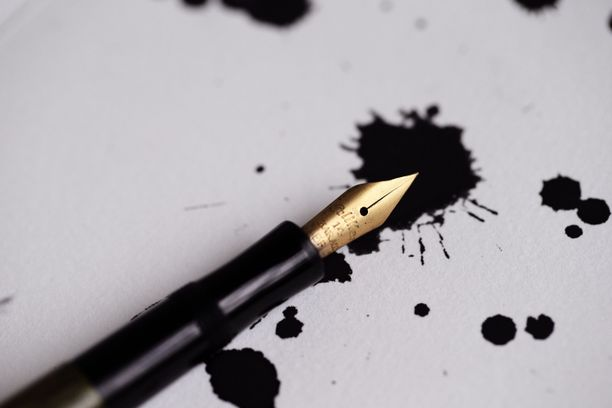 Black fountain pen with golden tip laying on white paper with black ink blots on it.