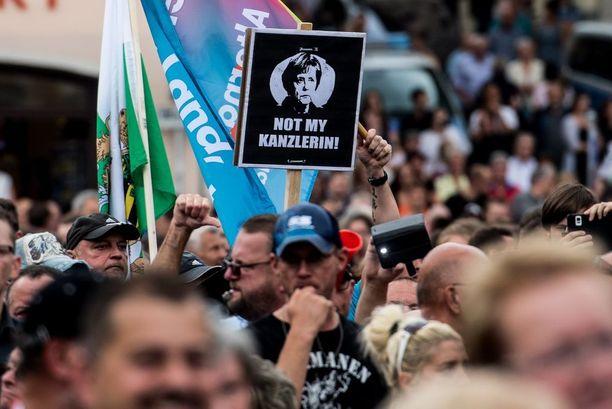 """Vastustajat huusivat ja kantoivat """"Ei minun kanslerini"""" -kylttejä konservatiivipuolueen kampanjatapahtumassa Annaberg-Buchholzissa."""