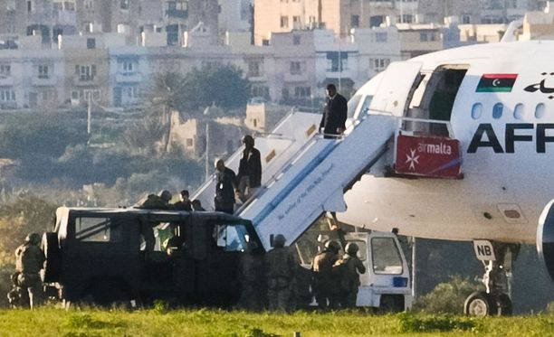 Vihreää lippua kantava lentokonekaappaaja antautuu Maltan viranomaisille.