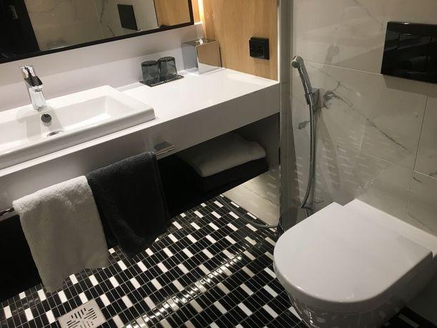 Kylpyhuoneessa on kahdenvärisiä pyyhkeitä, valkeita ja harmaita. Niin kahden hengen huoneessa kummallekin asukkaalle on omansa, eivätkä ne sekoitu.