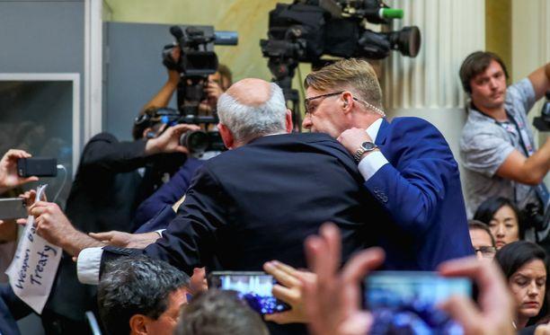 Suomalainen ja yhdysvaltalainen turvallisuushenkilöstö saattoi Husseinin pois lehdistötilaisuudesta.