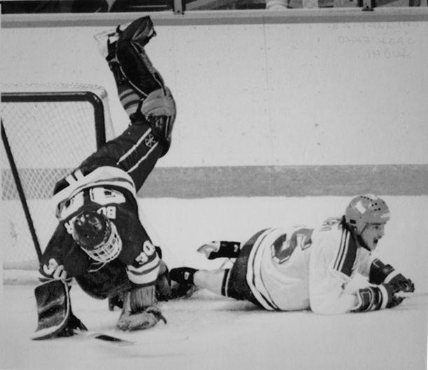 Olympiataistelua talvella 1988. Suomen Iiro Järvi kaataa Sveitsin maalivahdin Richard Bucherin.