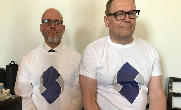 Sinisten vaalipäällikkö Pekka Sinisalo (vasemmalla) ja puoluesihteeri, kansanedustaja Matti Torvinen poseerasivat uudet logot paidoissaan.