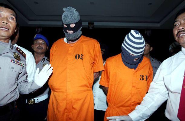Indonesian poliisi talutti epäiltyjä David Foxia (vas.) ja Giuseppe Serafinoa poliisiasemalla Balilla maanantaina.