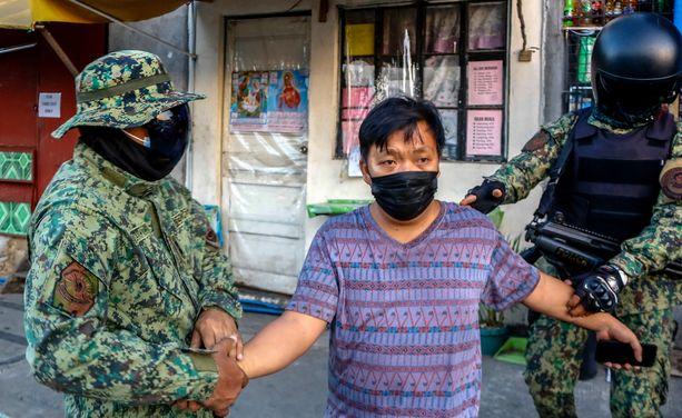 Poliisi pidättämässä koronakaranteenin rikkojaa Filippiinien pääkaupungissa Manilassa.