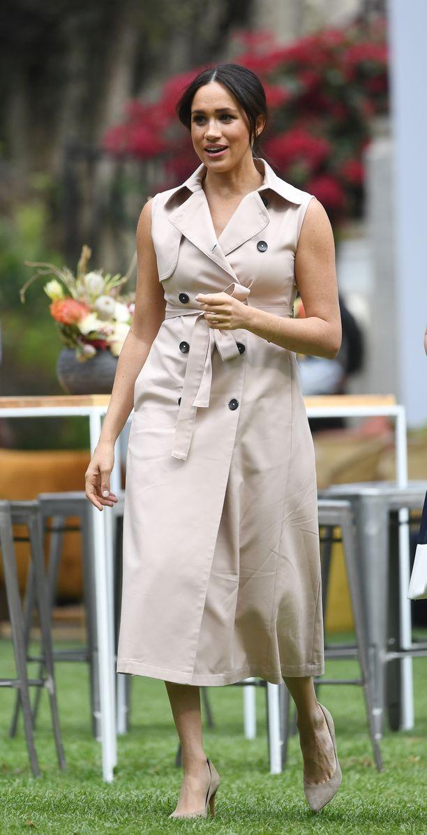 Meghan edusti Johannesburgissa suosikkimekossaan. Tyylikäs midimittainen trenssimekko toimii hyvin samansävyisten korkkareiden kanssa.