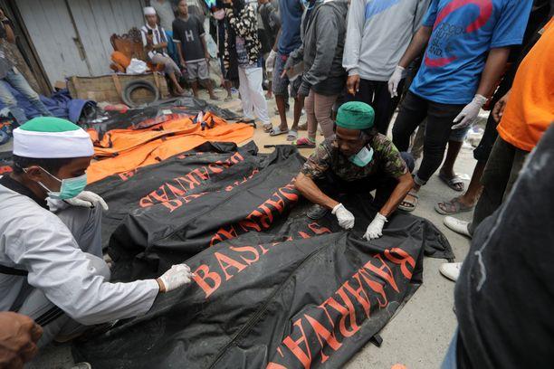 Pelastusvoimat tunnistivat sunnuntaina ruumiita, jotka kuljetettiin sen jälkeen joukkohautoihin.