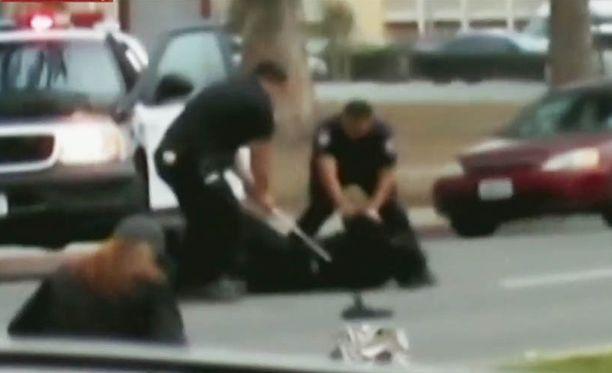 Kuvakaappaus videosta, jossa poliisit pamputtavat miestä.