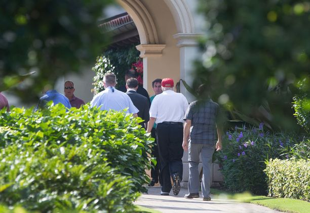 Presidentti Trump poistumassa seurueineen Jupiterin Trump National Golf Clubilta 24.11.2017.