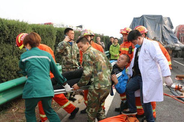 Pelastajat kantoivat loukkaantunutta pois moottoritieltä.