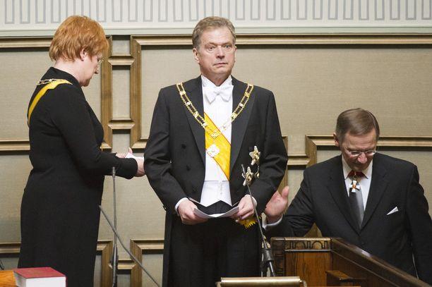 Tältä näytti eduskunnassa tuoreen presidentin virkaanastujaisissa vuonna 2012. Kuvassa Niinistö presidentti Tarja Halosen ja ulkoministeriön protokollapäällikkö Mikko Jokelan kanssa.