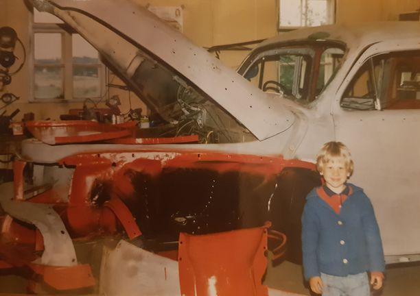 Mikko Selivaaran poika Antti poseeraa kunnostettavan auton edessä isän verstaalla vuonna 1984.