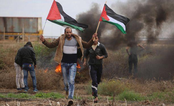 Mielenosoittajat ovat heiluttaneet Palestiinan lippuja yhteenotoissa israelilaissotilaiden kanssa.