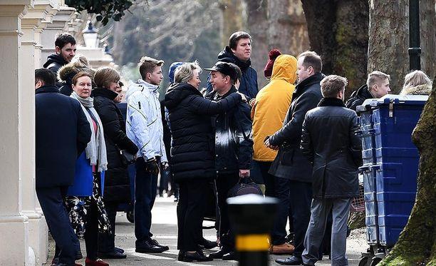 Venäjän suurlähetystön karkotettuja henkilöitä perheineen hyvästelemässä kollegoitaan lähestystön edessä Lontoossa tiistaina.
