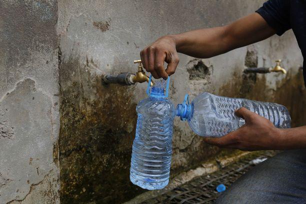 Kuvassa mies täyttää pulloja vedellä Jemenissä kesäkuussa 2019. Kuvituskuva.