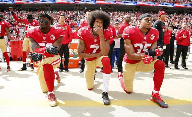 Colin Kaepernick (keskellä) aiheutti vuonna 2016 valtavan kohun polvistumalla Yhdysvaltain kansallislaulun aikana.