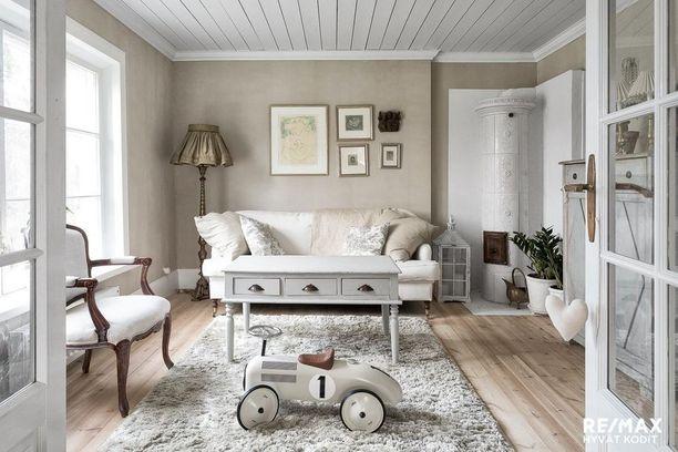 Maalaisromanttisessa sisustuksessa pehmeät tekstiilit ovat isossa roolissa. Kauniit huonekalut ja ihastuttava kakluuni ovat tämän olohuoneen kulmakivet.