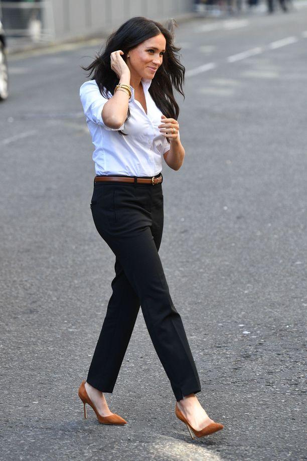 Meghan itse oli pukeutunut myös malliston tuotteisiin: klassisiin mustiin suoriin housuihin ja valkoiseen paitapuseroon.