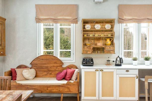 Vanha puusohva kutsuu keittiöön viihtymään. Työtasojen yläpuolelta avautuva metsämaisema lisää tunnelmaa maalaisromanttiseen sisustukseen