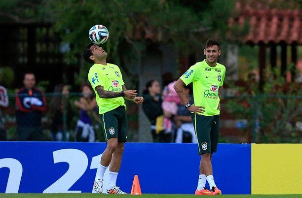 Neymar ihastelee kun Barcelonan joukkuekaveri Dani Alves kesyttää palloa.