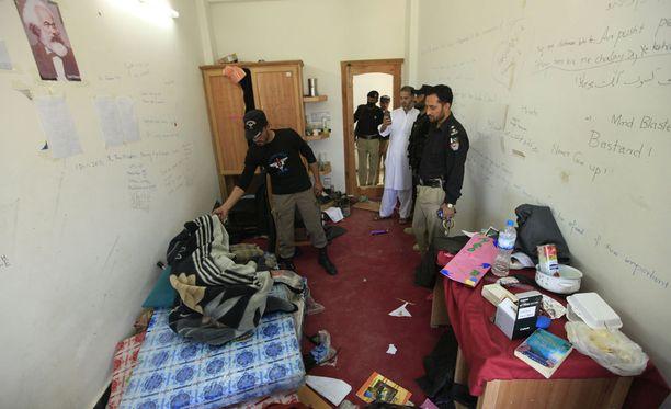 Poliisit tutkivat väkijoukon murhaaman opiskelijan asuntolahuonetta.