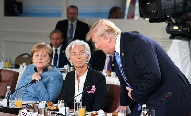 Saksan liittokansleri Angela Merkel ja IMF:n johtaja Christine Lagarde reagoivat, kun Trump saapuu myöhässä tasa-arvoa käsittelevään aamiaispalaveriin G7-kokouksessa.