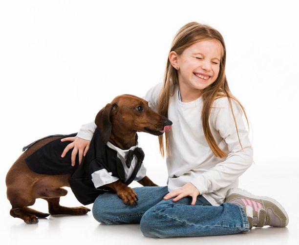 Lapsi nauraa, mutta koira lipoo kuonoaan häntä jalkojen välissä, korvat taaksepäin suuntautuneina ja selkä kyyryssä.