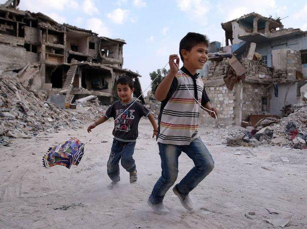 Lapset leikkivät Dahaniyan naapurustossa pääkaupunki Damaskoksessa lokakuussa 2015. Talot ovat muuttuneet kivimurskaksi, mutta lasten ilo on kuolemasta ja kärsimyksestä huolimatta tallella.