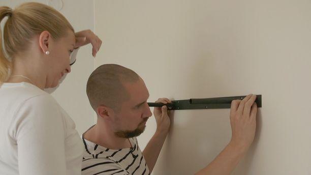 Ensitreffit alttarilla -pariskunta laittaa hyllyä seinään.