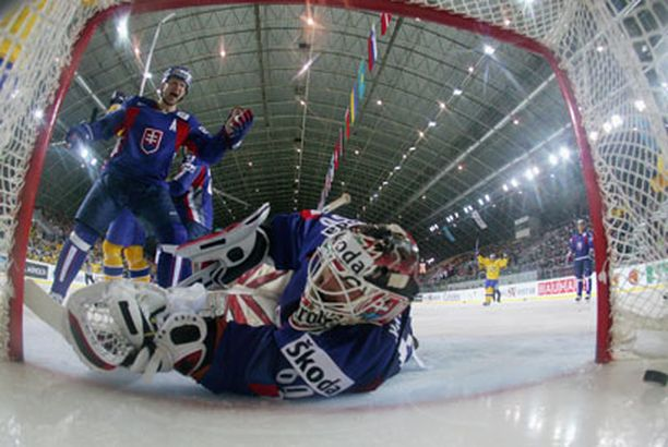 Slovakian Martin Strbak tuulettaa, kun kiekko uppoaa Ruotsin Daniel Henrikssonin taa.