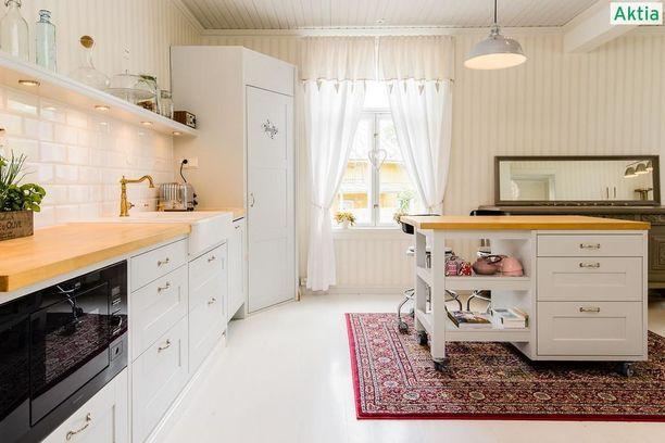 Tähän keittiöön on tuotu vanhan talon tunnelmaa lukuisilla yksityikohdilla kuten peiliovellisilla kaapistoilla, tiililadonnalla ladotuilla laatoilla ja vaaleilla puutasoilla. Liikuteltava saareke palvelee tarvittaessa niin aamiaispöytänä kuin lisätyötasona.
