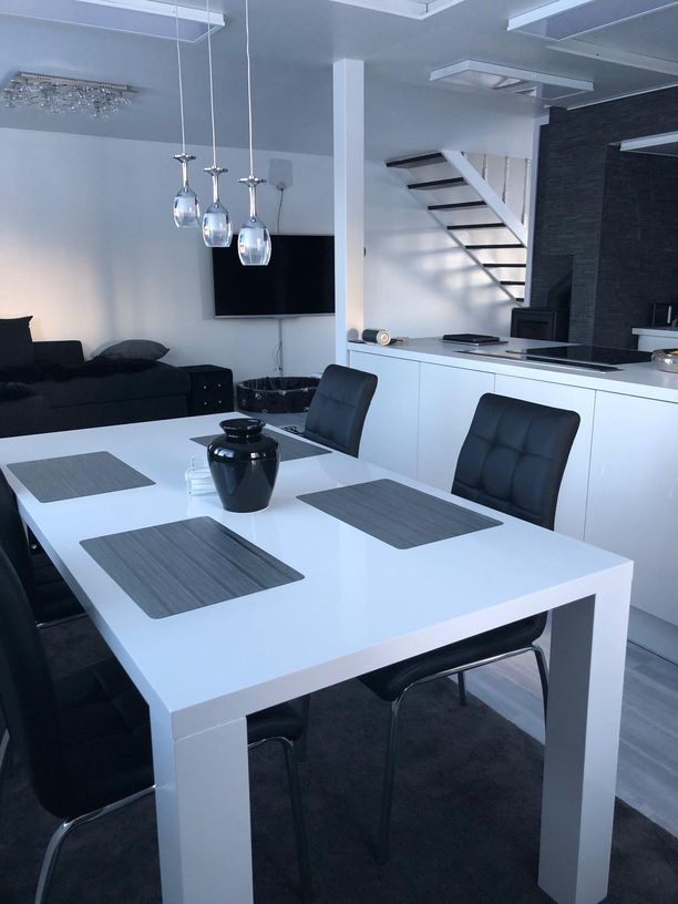 Valkoinen pöytä, mustat tuolit, valkoiset, keittiötasot, musta sohva ja musta rohea seinä. Ei jää epäselväksi, mistä väreistä Rita ja Aki tykkäävät.